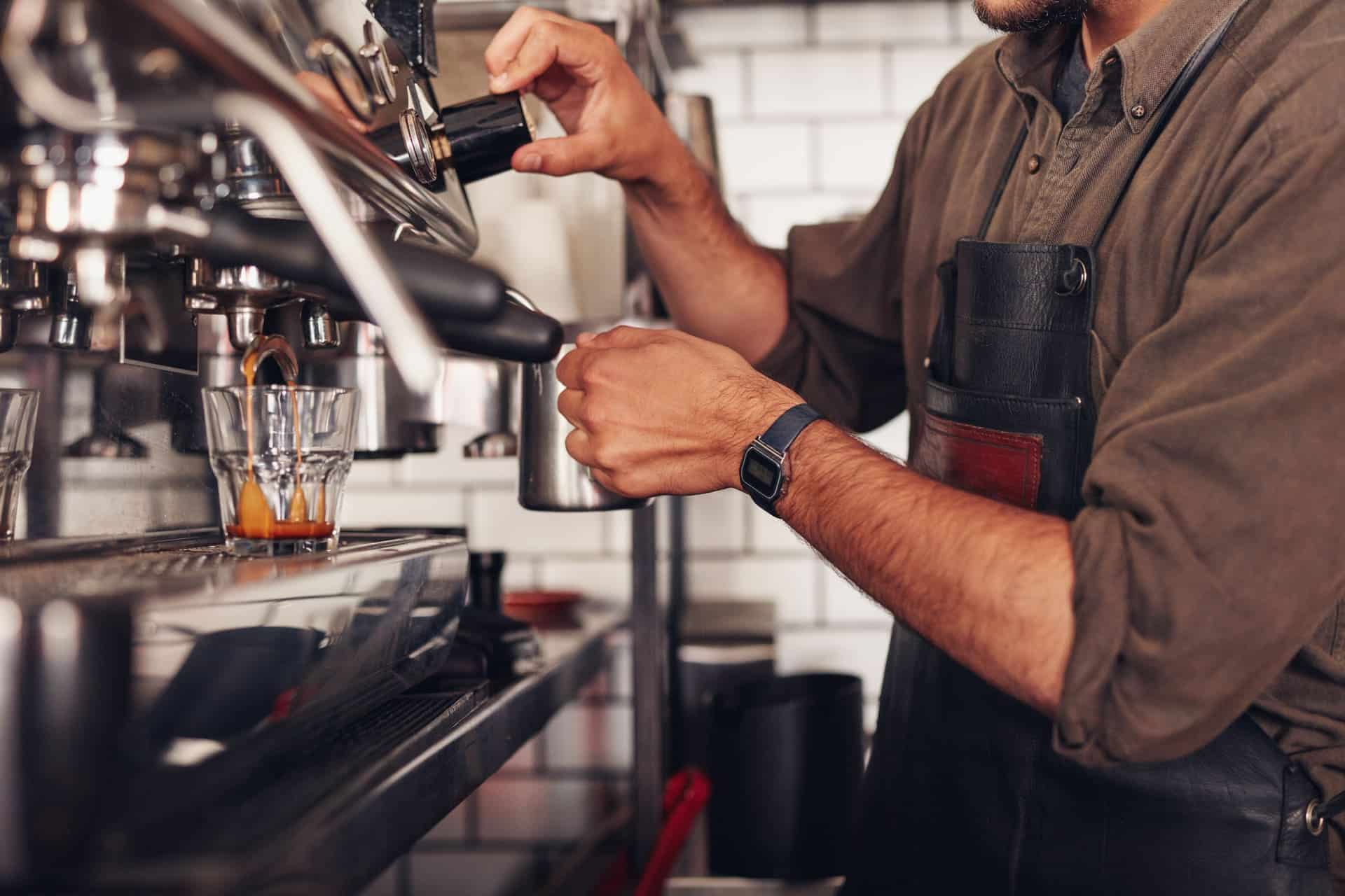 barista making coffee using a coffee maker PGK3YJF