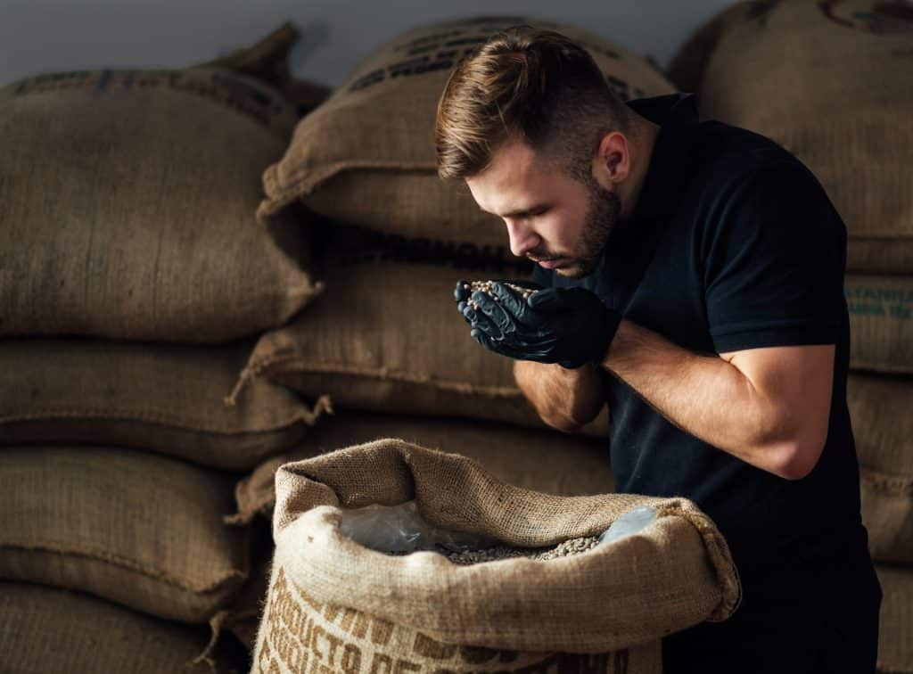 young worker sniffing a fistful of fresh raw beans WUZGNCJ